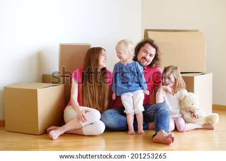 Happy young family sitting on a floor in their new home - stock photo