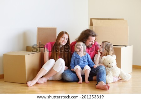 Happy young family sitting on a floor in their new home