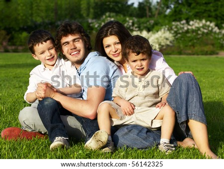 happy young family sitting on grass