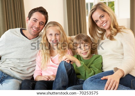 Happy young family sitting on sofa - stock photo