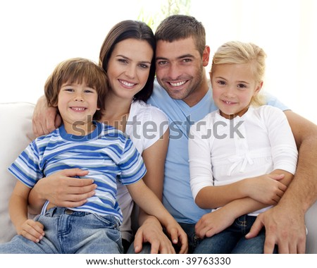 Happy young family sitting on sofa at home - stock photo