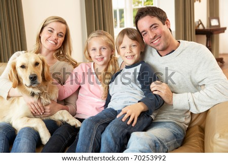 Happy young family sitting on sofa holding a dog