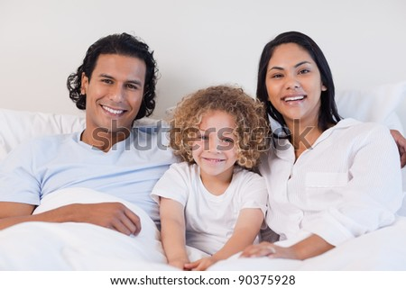 Happy young family sitting on the bed together - stock photo