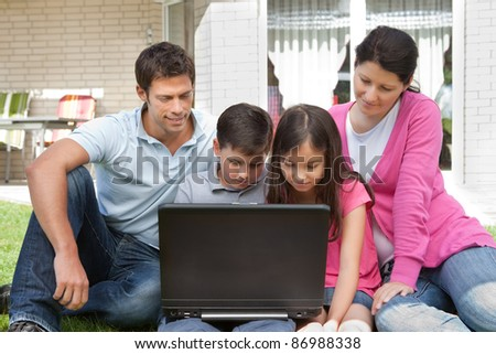 Happy young family sitting outside their house using laptop