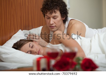 Happy young family sleep in the bed at home. Valentine's Day. - stock photo
