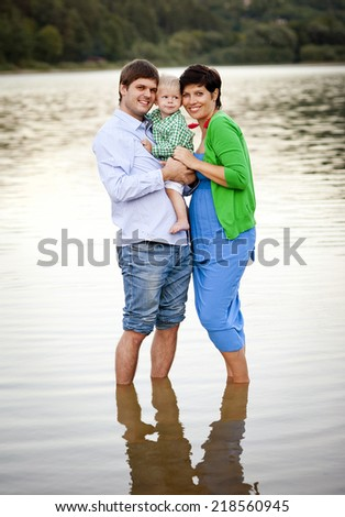 Happy young family spending summer time together by the lake on the sandy beach - stock photo