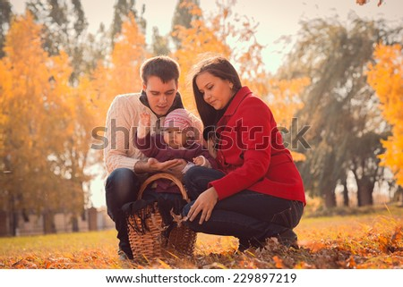 happy young family spending time  outdoor in the autumn park - stock photo