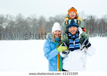 happy young family spending time outdoor in winter (focus on the father)