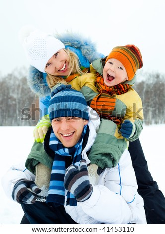 happy young family spending time outdoor in winter park - stock photo