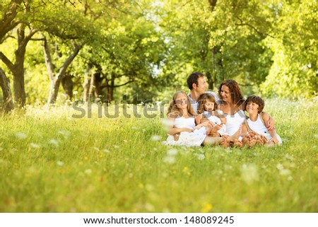 Happy young family spending time outdoor on a summer day - stock photo