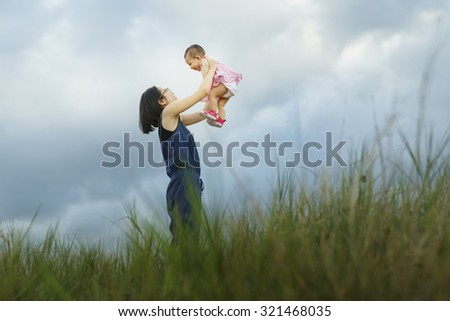Happy young family spending time outdoor on a summer day - Vibrant color effect - stock photo