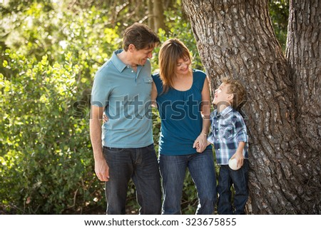 Happy young family standing outside - stock photo