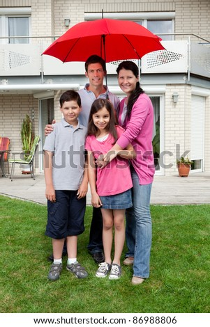 Happy young family standing under one umbrella outside their house