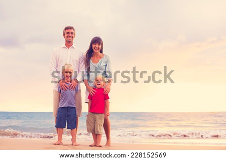 Happy Young Family Together on the Beach at Sunset - stock photo