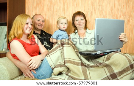 Happy young family using  laptop in the living-room - stock photo