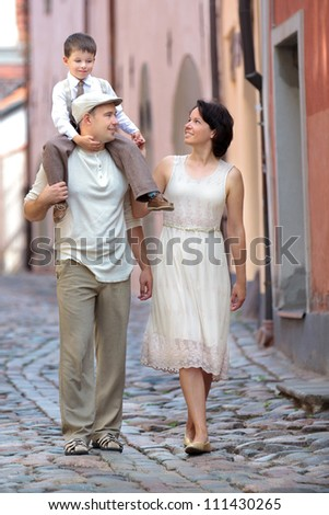 Happy young family walking in city street - stock photo