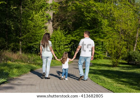 Happy young family walking in the park. Healthy lifestyle concept