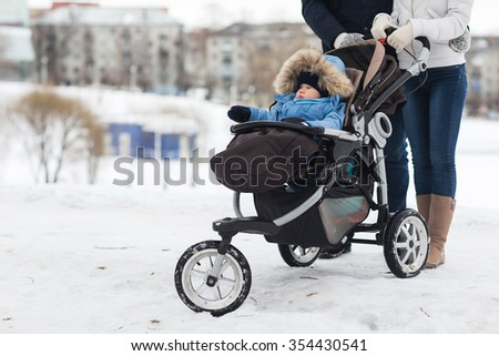 Happy young family walking in the park in winter. The parents carry the baby in a stroller through the snow. - stock photo