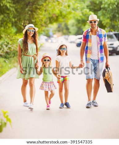 Happy young family walking with guitar spending carefree time together. Travel and holiday concept - stock photo