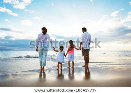 Happy young family watching the sunset at the beach.  Happy Family Lifestyle  - stock photo