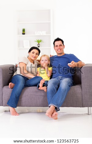 happy young family watching tv on sofa at home