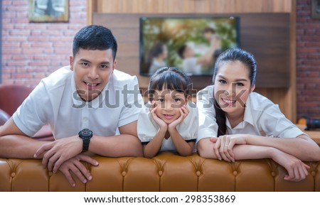 happy young family wathching flat tv at vintage home indoor - stock photo