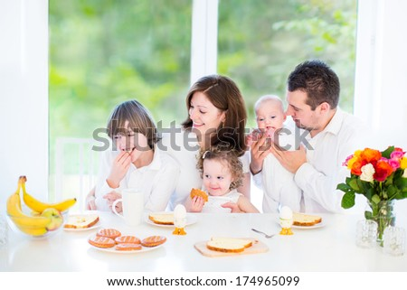 Happy young family with a teenage boy, cute curly toddler girl and a newborn baby having fun together on a Sunday morning having breakfast in a white dining room with a big window - stock photo
