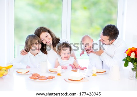 Happy young family with a teenage boy, cute curly toddler girl and a newborn baby having fun together during an Easter breakfast in a white sunny dining room with a big garden view window - stock photo