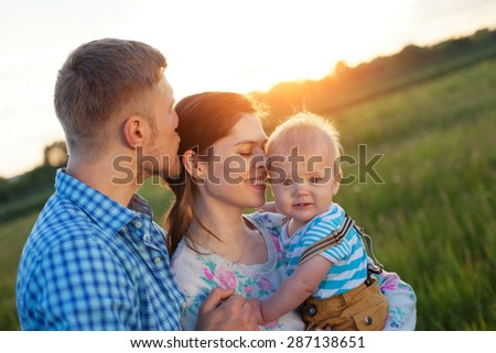 happy young family with baby spending time outdoors (intentional sun glare, lens focus on mother) - stock photo