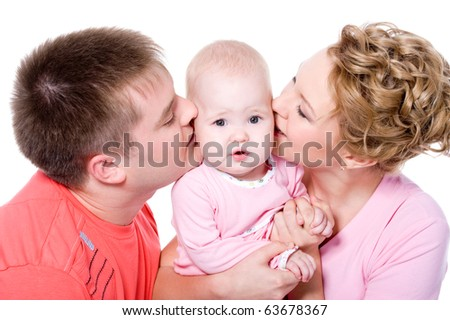 Happy young family with beautiful baby on white background. Parents kiss the child - stock photo