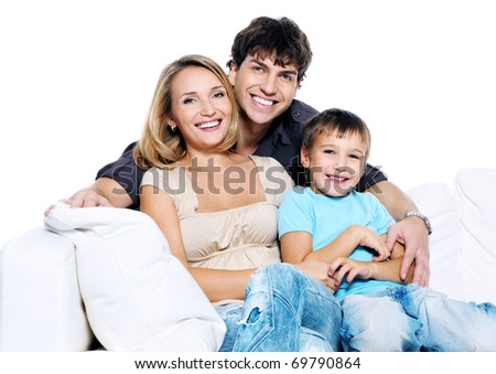 Happy young family with child siting on white sofa isolated - stock photo