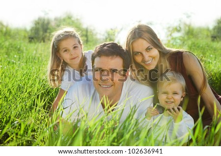 Happy young family with children outdoors - stock photo