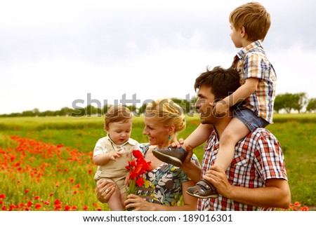 Happy young family with children resting outdoors in poppies field - stock photo