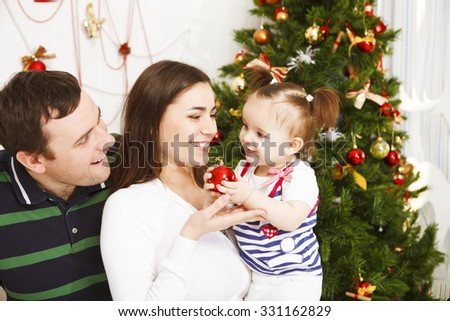 Happy young family with Christmas baby near the Christmas tree