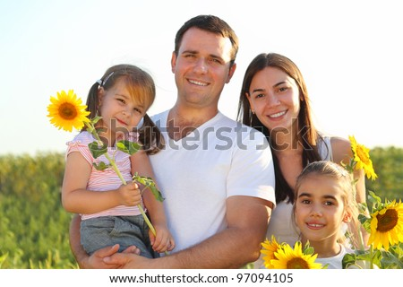 Happy young family with daughters holding sunflowers - stock photo