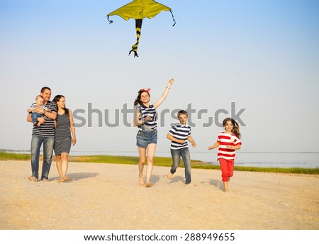 Happy young family with flying a kite on the beach. Summer vacation