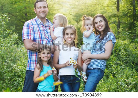 Happy young family with four children in the spring forest