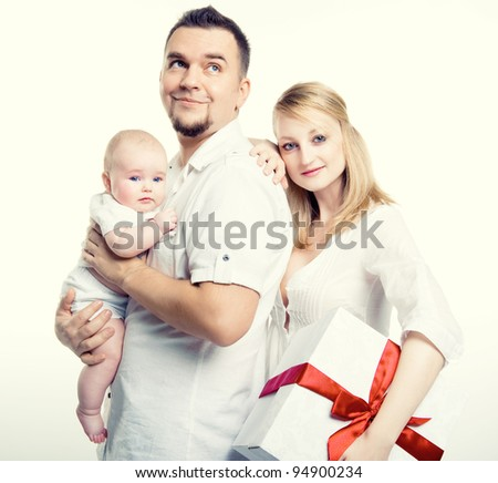Happy young family with gift box over white background - stock photo