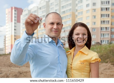happy young family with key  in front of new home - stock photo