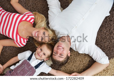 happy young family with kids in bright modern living room have fun and looking big flat lcd tv - stock photo