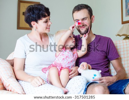 Happy young family with little child at home - stock photo