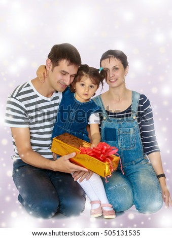 Happy young family with little daughter cuddling together in celebration of Christmas.Purple Christmas background with white snowflakes.