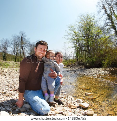 Happy young family with little daughter near the mountain river outdoors