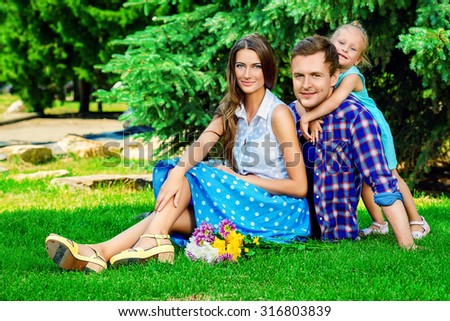 Happy young family with little daughter resting together at the park. Summer day. - stock photo