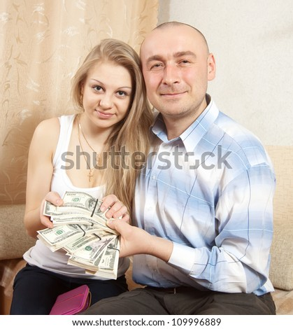 Happy young family with many US dollars  in home - stock photo