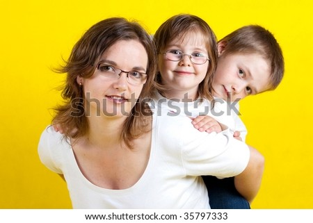 Happy young family with mother,  daughter and son - yellow background - studio photo