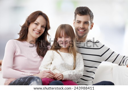 Happy young family with preschool daughter sitting at sofa in living room.