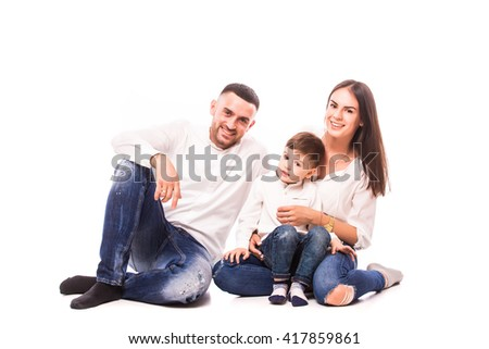Happy young family with pretty child posing on white background - stock photo