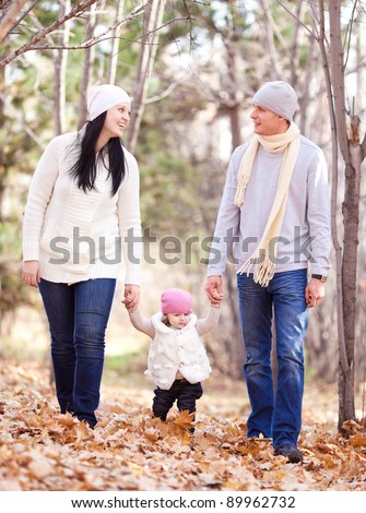 happy young family with their daughter spending time outdoor in the autumn park - stock photo