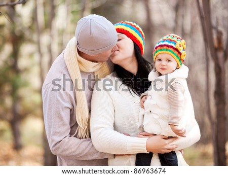 happy young family with their daughter spending time outdoor in the autumn park (focus on the baby)